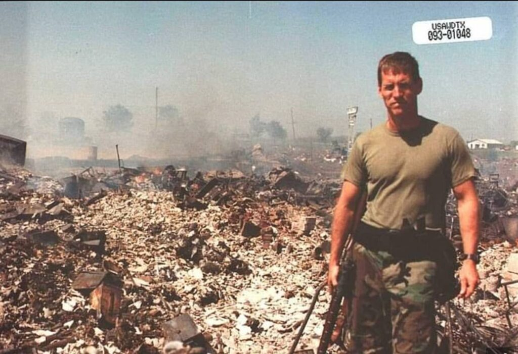 David Chipman posing in front of the aftermath of the seige in Waco, Texas